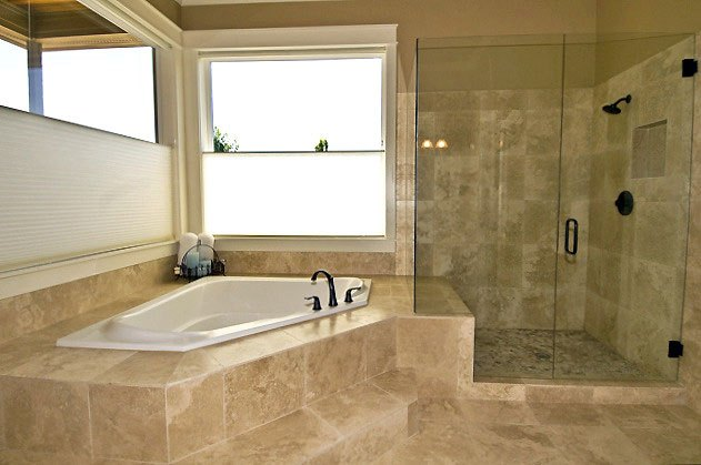 white ceramic bathroom with soaking tub and glassed in shower