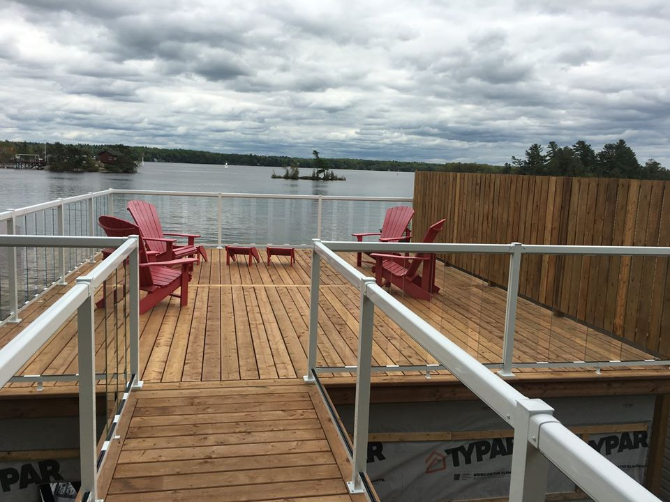 four red deck chairs overlooking a lake