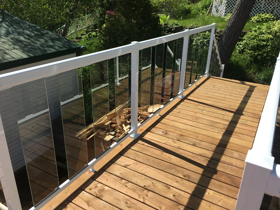 a wooden deck with a glass fence with white railings
