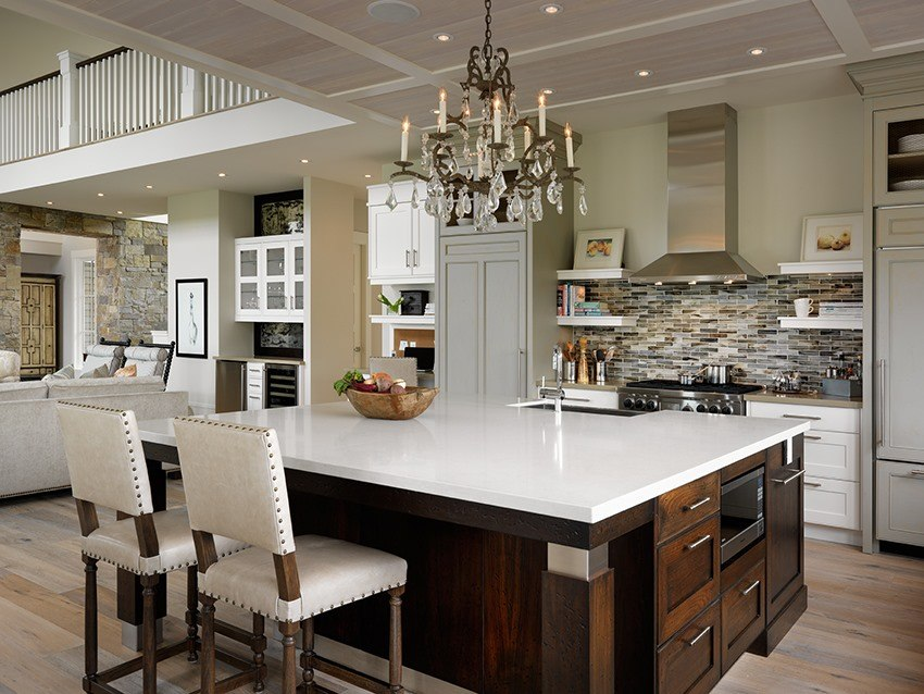 a candle stick chandelier above a large kitchen island with a white countertop