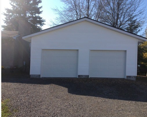 a white two car garage with a gravel driveway