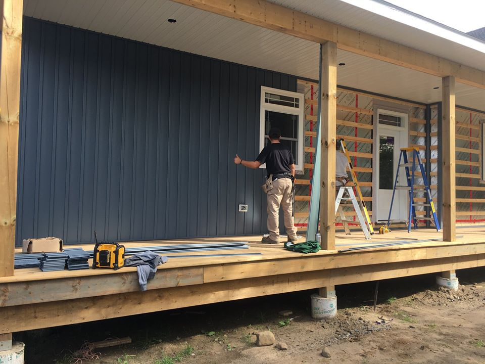 man in black shirt and beige pants working on the siding of a home