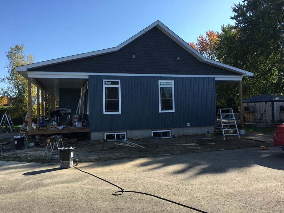 exterior photo of a one story home with blue siding