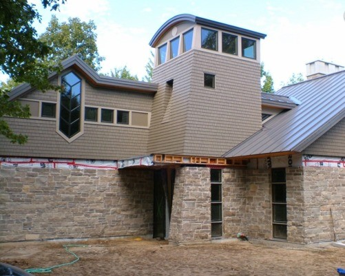 a two story home under construction with beige stone exterior