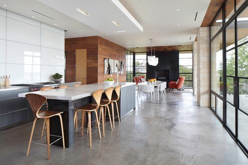 a large open concept kitchen with a concrete kitchen island and concrete floors