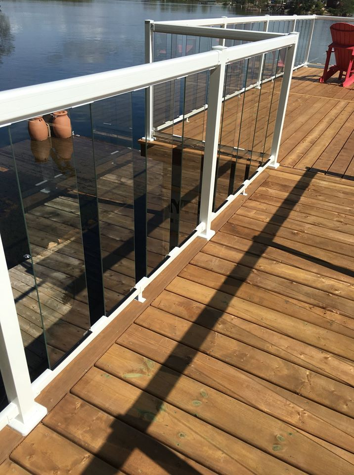 a wooden deck with a glass fence and white railing