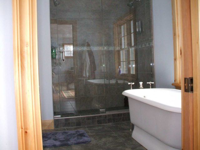 white soaking tub in a bathroom with glass shower doors